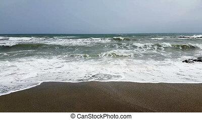 Waves breaking on a rocky beach with white foam