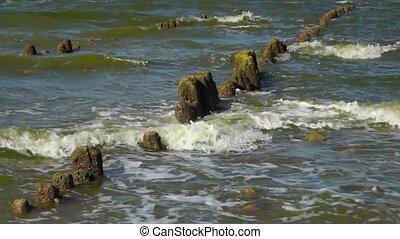 Waves breaking on old pier