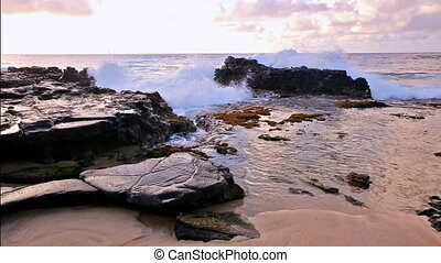 waves breaking on rocks close to Sandy beach, Oahu, Hawaii -...