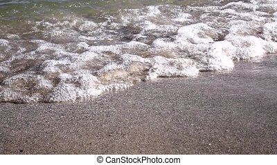 Waves breaking on the sand on the beach. Slow motion. Close up