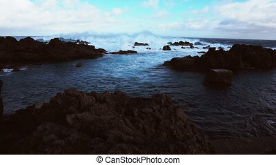Waves breaking over volcanic rocks in biscoitos - Wide angle...