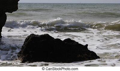 Waves burst over rocks in the Algarve, Portugal