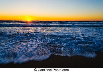 Waves by the shore at sunset in motion blur effect
