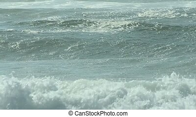 Waves crash on shore in afternoon light on a sandy beach in Portugal.