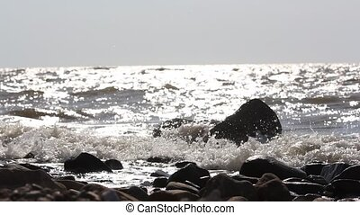 Waves crashing against stones and sunlight reflected in...