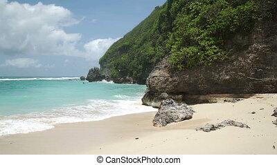 Waves crashing against the rocks of Ungasan Coast of Bali -...