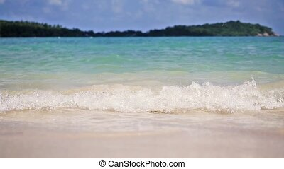 Waves crashing gently on quiet sandy beach in Koh Samui....