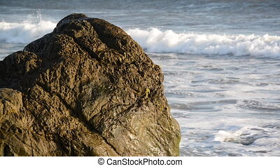 Waves Crashing into a Large Boulder - Waves crashing into a...