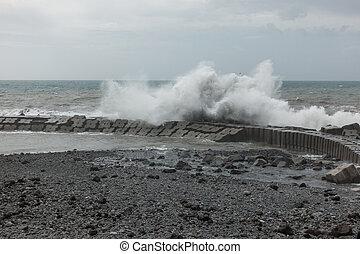 Waves crashing on a pier in Ponta do Sol, Madeira