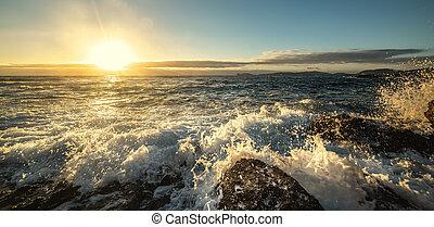 Waves crashing on Alghero rocky shore at sunset