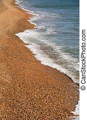 Waves crashing on pebble shore