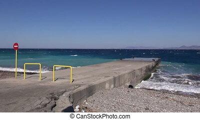 Waves crashing on pier in Rhodes