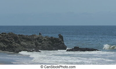 Waves Crashing On Rock Peninsula - Steady, wide shot of a...