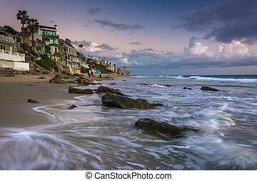 Waves crashing on rocks and beachfront homes in Laguna Beach, Ca