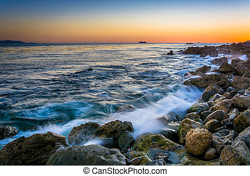 Waves crashing on rocks at Pelican Cove at sunset, in Rancho...