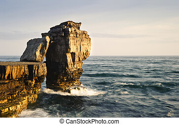 Waves crashing over rock formation cliffs at sunset with beautiful light on rock faces