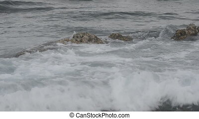 Waves Crashing over Submerged Rock - Waves wash over an...