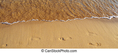 Waves erasing the footprints in the beach sand