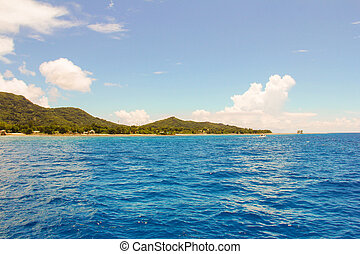 Waves from boats and view of the Mahe island