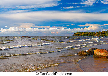 Waves, granite stone, evening clouds. Evening landscape on the Gulf of Finland.