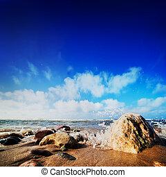 Waves hiting rocks on the sunny beach