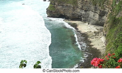 Waves hitting rocks on tropical beach forming splash shape,...
