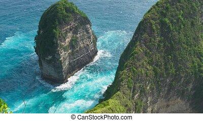 Waves in ocean around the rocks formation on Kelingking...