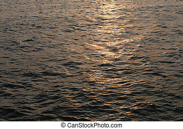 Waves in sea and light of sunset.