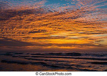 Waves in the Atlantic Ocean and sunrise, at Folly Beach, South Carolina.