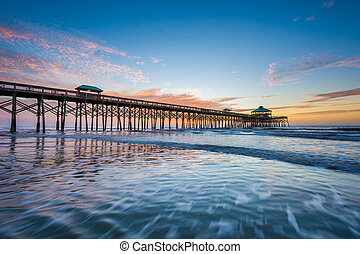 Waves in the Atlantic Ocean and the pier at sunrise, in Folly Beach, South Carolina.