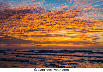 Waves in the Atlantic Ocean at sunrise, in Folly Beach, South Carolina.