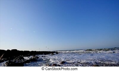 waves in the sea and flying seagulls near rocks and mountains on the blue sky background