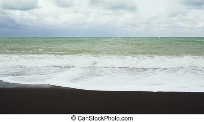 Waves in the troubled sea collapse on the shore with black...
