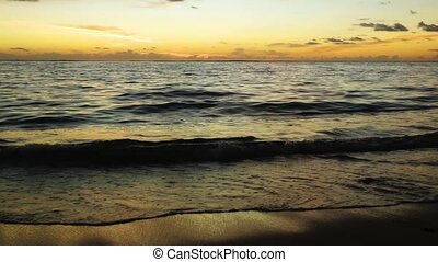 Gentle waves roll over the fine, tropical sand as sunset approaches at this tropical beach paradise, with sound.