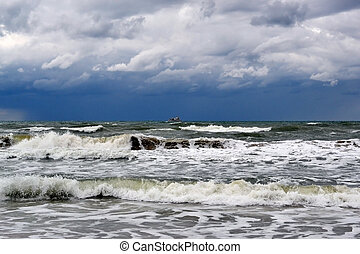 Waves of the Black Sea and the ship on the horizon in rainy weather.