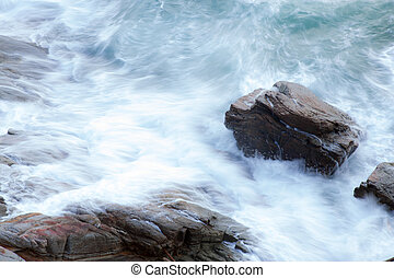 waves of the ocean crashing into the rocks.