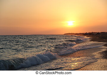 Waves of the sea on the sandy beach at sunset