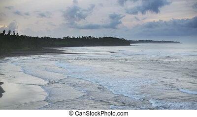 waves of the sea roll on the stony coast, Bali, Indonesia -...