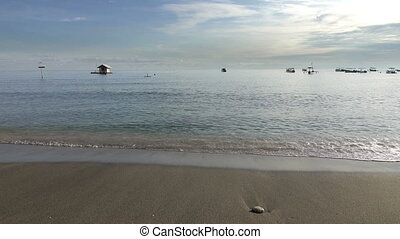 Waves of the warm sea run on the sandy beach early in the morning, Pemuteran Bali