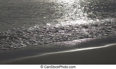 Waves of the warm sea run on the sandy beach early in the morning,slow motion