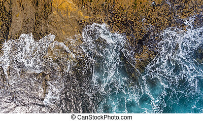 Waves of turquoise water washed by the rocky stone coast of Portugal. Aerial view.