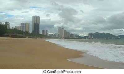 Gentle waves wash the coarse sand of a popular beach, with the tall buildings of Nha Trang, Vietnam in the background. Footage UHD