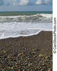 Waves with white foam on a pebbles beach