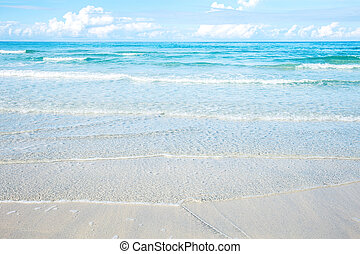 Waves on beach with sunlight.