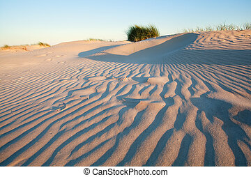 waves on sand dune at sunset