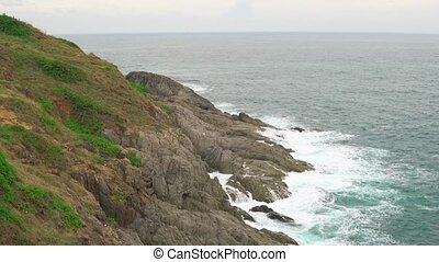 Waves on the azure water in the tropical sea. An island with a rocky shore and green plants