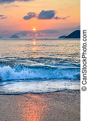 Waves on the seashore and sun from the clouds at dawn with reflection in water