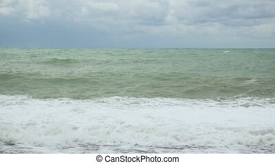 Waves on the shore in the gray-green sea