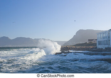 Waves ounding the coast directly in front of a seaside home. Kalk Bay, South Africa