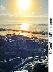 waves over hot sunset rocks